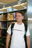 A young student in the library with a backpack poster