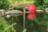 red color umbrella at the pond side poster