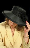 Middle aged woman underneath a black hat.