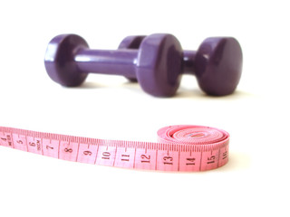 measuring tape and dumbbell over white background