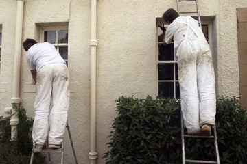 Two painters decorating the exterior of a house.