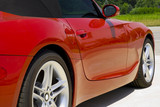 Looking down the side of a red convertible  roadster car .   poster
