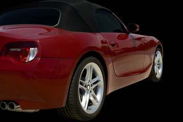 Red convertible sports car roadster  isolated on a black.