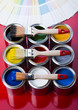 colorful brushes and cans on the red background