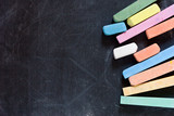 closeup of blackboard with pieces of coloured crayons poster