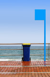 colorful containers for trash on the beach under blue sky poster