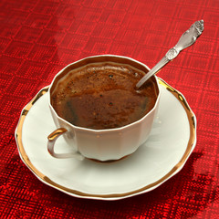 Cup of coffee with the spoon on a red background