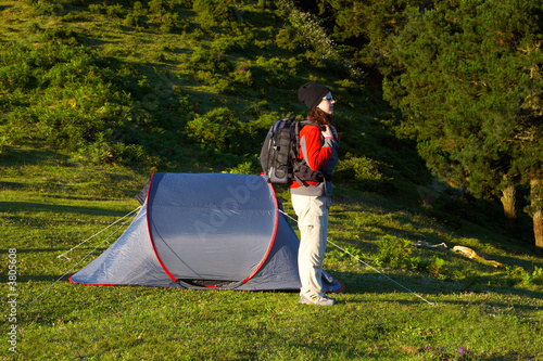 A girl with the black backpack next to her tent in the meadow