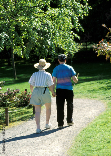 Blind couple walking in a park together.