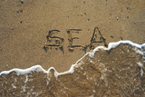 Sea script on sand, waves washing it poster