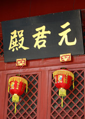 Chinese sign above hanging lanterns