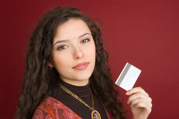 Young woman showing credit card isolated on red