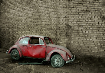 Grunge car in front of a brick wall with copy space