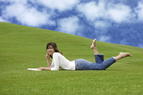 Beautiful woman lying on the grass and reading poster