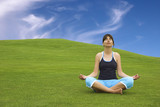 Beautiful athletic woman making yoga on a beautiful green meadow
