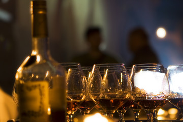 Wineglasses with cognac, a bottle, and evening party outside
