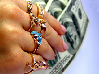 Dollars in woman's hand with gold rings
