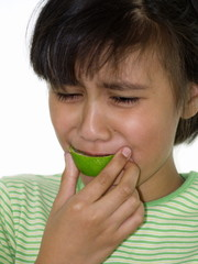 mädchen beißt in eine saure Limone