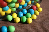Different coloured sweets in a glass bowl and on the textile poster