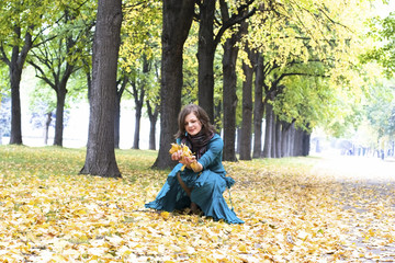 Girl sitting on the yellow leaves