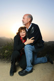 Mature couple embracing outdoors at sunset poster