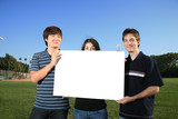 Three young friends holding a blank white billboard  poster