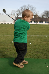 Young boy practising his golf on the driving range