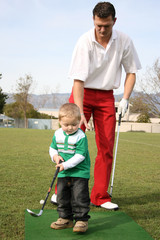 Father and son practising on the golf driving range