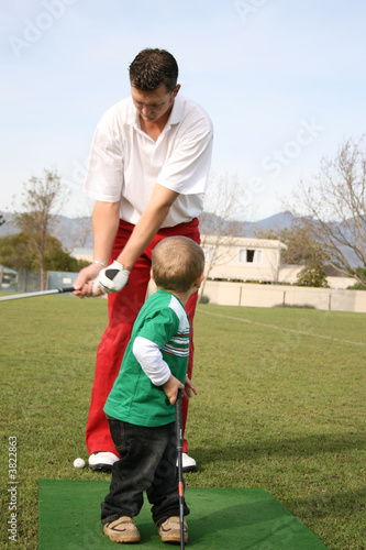 poster of Young boy admiring his dad on the golf range