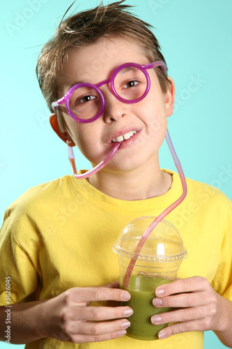 Boy drinks a healthy juice with wheatgrass, barleygrass and