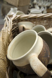 Ceramic handmade cups in the basket on the countryside market poster