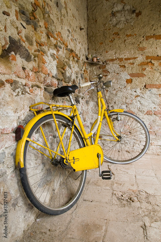 Old yellow bike on the wall - 3827483