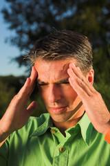 man with migraine close up portrait outdoor