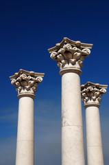 Three ancient greek pillars against a blue sky