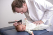 Pediatrician performing a physical exam on a healthy newborn.