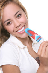 A pretty young woman eating a popsicle
