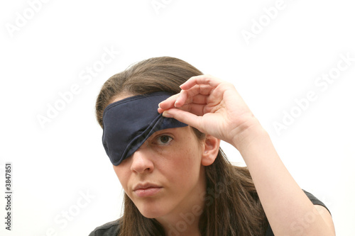 Woman wearing a blindfold isolated over white