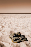 A pair of sandals on a sandy beach selectively desaturated