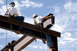 Two ironworkers atop the skeleton of a modern building - 3851682
