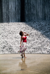 A woman awestruck with the splendor of a cascading  waterfall