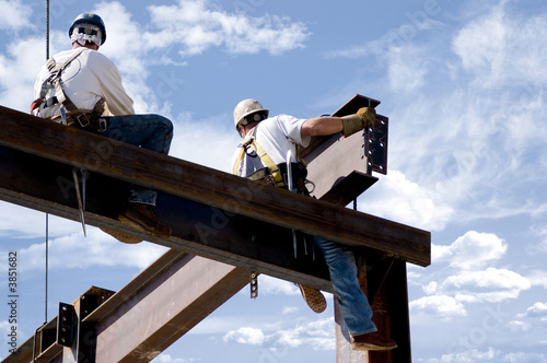 Two ironworkers atop the skeleton of a modern building