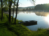 Pond during the sunrise with a old boat and mist poster