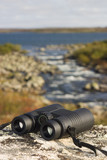 binocular on a hilltop overlooking a lake poster