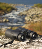 binocular on a hilltop overlooking a lake