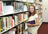 A cute teen girl at the school library. poster