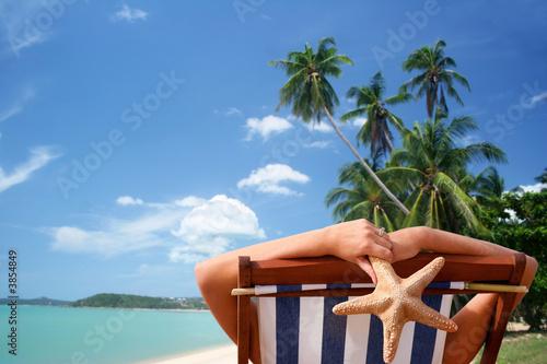 Mujer tomando el sol en una playa tropical
