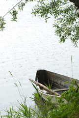 Lonely boat on coast of lake during a rain