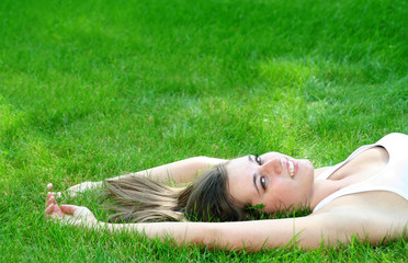 Beautiful young woman lying on a lawn