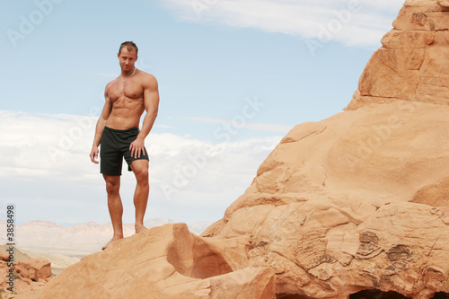 Muscular man on red rocks