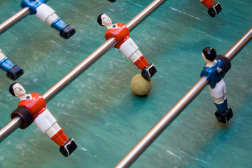 Detail of foosball table with toy players and yellow ball